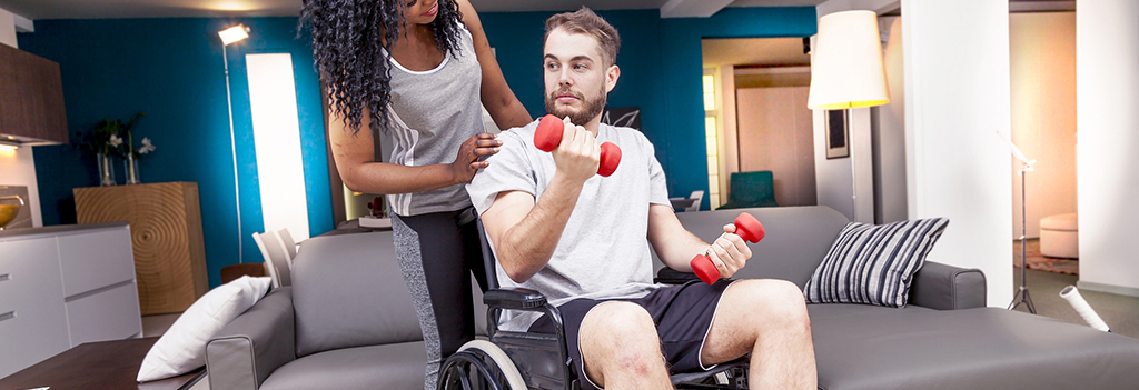 A trainer assists a man in a wheelchair as he lifts weights.
