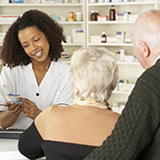 A pharmacist discusses medication with an older couple.
