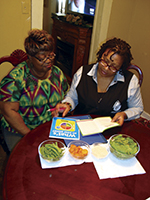 Two women at a table review educational materials,  represent community health workers engaging to prevent cardiovascular disease.