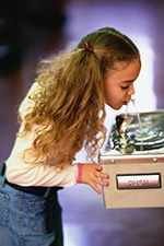 A young girl drinks from a public water fountain.