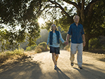 An older couple walking along a pathway in the woods