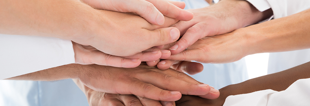 A group of stacked hands representing a team of team-based care health professionals.