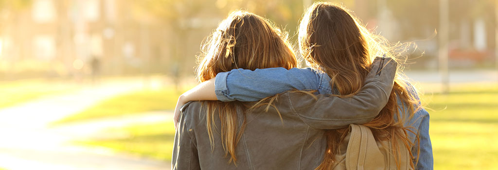 Two college aged females walking with arms around each other for emotional support.
