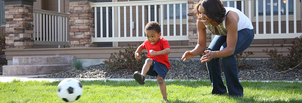 A mom and young son kick a soccer ball in the front yard of their house.
