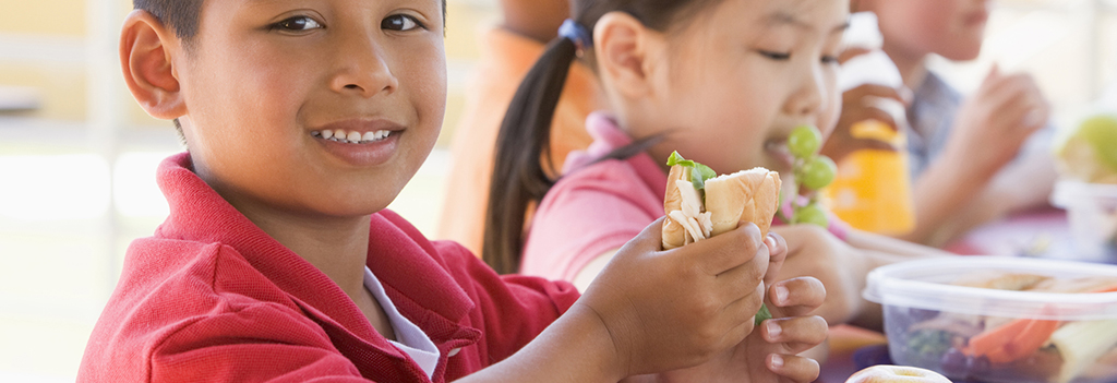 School children eat healthy lunches that include fruits and vegetables.
