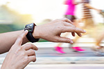 A runner checks heartrate on a wristwatch activity monitor.