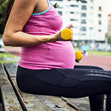A pregnant woman exercises with hand weights.