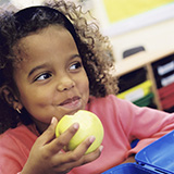 A young girl eats an apple in her classroom.