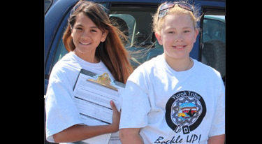 Two girls in t-shirts support motor vehicle injury prevention program among Yurok Tribe in California