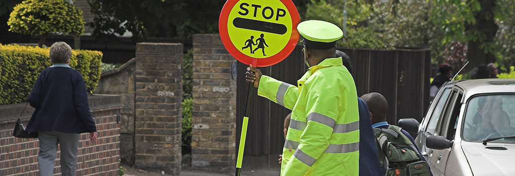 A crossing guard stops traffic as a parent and child cross the street going to school.