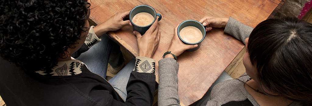 Two people have a conversation while drinking coffee.