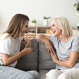 Two women sitting on a couch while talking.