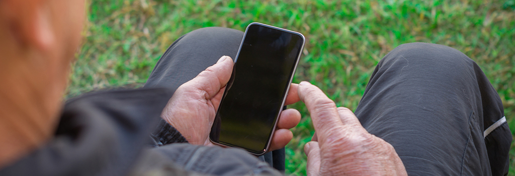 An elderly man looks at information on a smart phone.