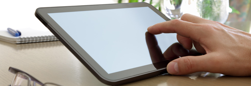 A finger touching a tablet computer screen