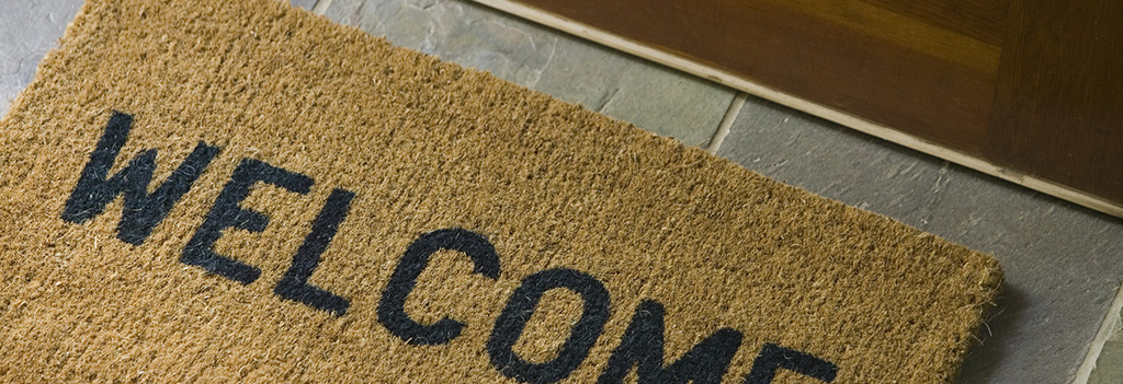 A mat that reads 'welcome' sits outside the front door to a home.