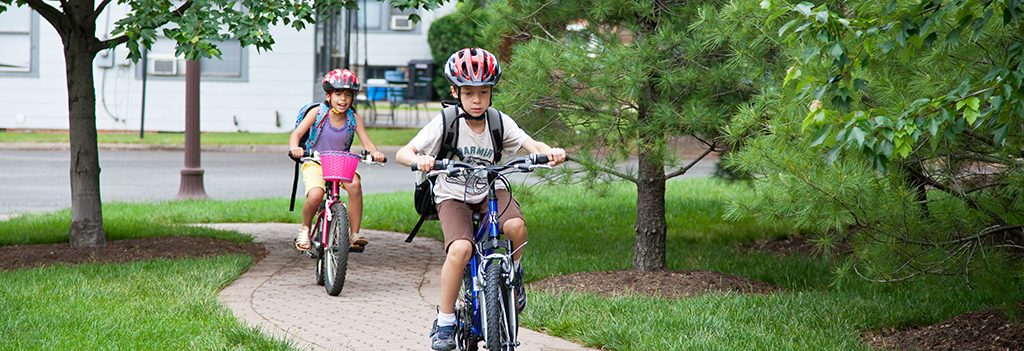 Two young children ride their bicycles on a bike path.