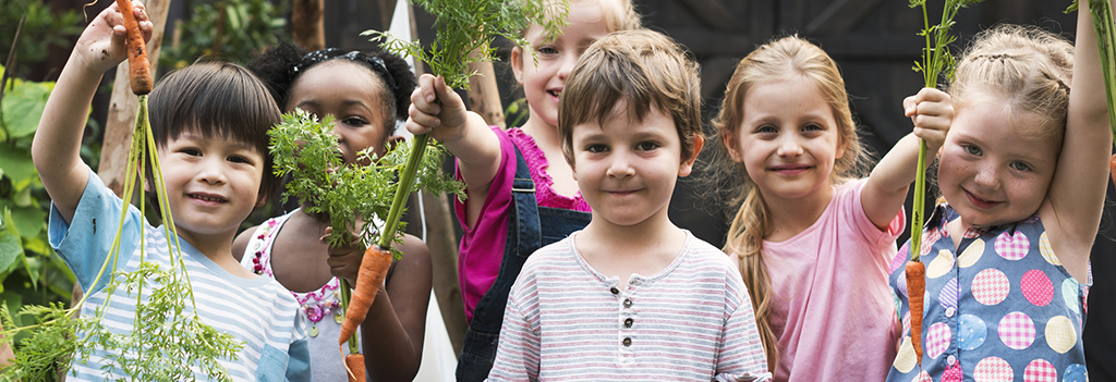 A group of children hold carrots dug from a garden.