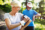 An older couple consult smart devices as they exercise.