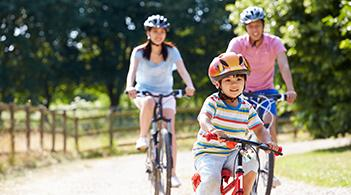 A family rides bicycles on a paved bike trail