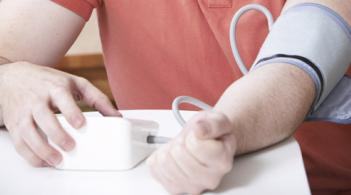 torso and arms of a person wearing a blood pressure cuff and holding an automated monitor
