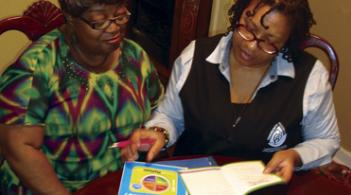 two women sitting at a table looking at papers and educational materials