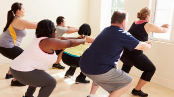 A group of overweight people participate in a fitness class