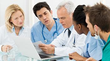 A team of doctors review a medical chart