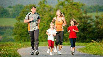 A family of four runs on a paved running trail