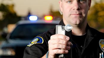 police officer standing in front of a police car holding up a breathilizer