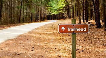 "path through a wooded area marked with a sign that reads, ""trailhead"" and has an arrow"