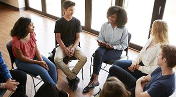 A counselor leads a discussion among a group of students.