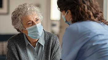 A home healthcare nurse meets with an elderly patient.