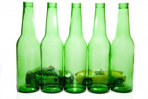 A police car and another car are seen through the green glass of empty beer bottles