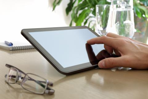 A finger touching the screen of a tablet computer