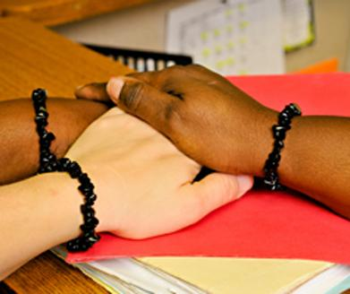 Three hands on a table. Each wrist has a black coral bracelet