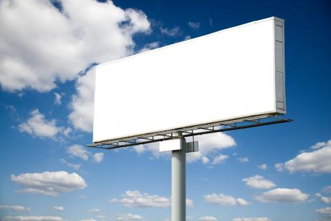 A blank highway billboard, with a blue sky behind it