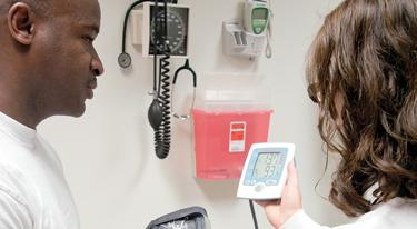 A nurse shows a male patient the readout of a digital blood pressure monitor