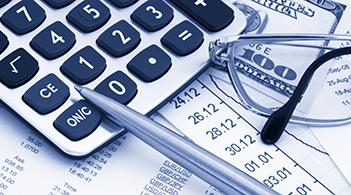 A calculator sits on a stack of hundred dollar bills. This represents the economic effectiveness of interventions to prevent cardiovascular disease and dental cavities.