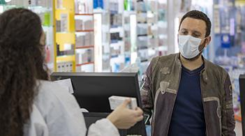 A pharmacist discusses medication with a patient.