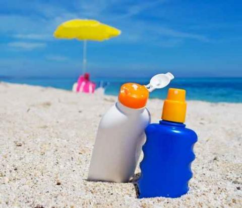 Two bottles of sunscreen sit upright in the sand of a beach, with the ocean in the background.