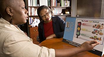 A community health worker discusses healthy eating with a patient.