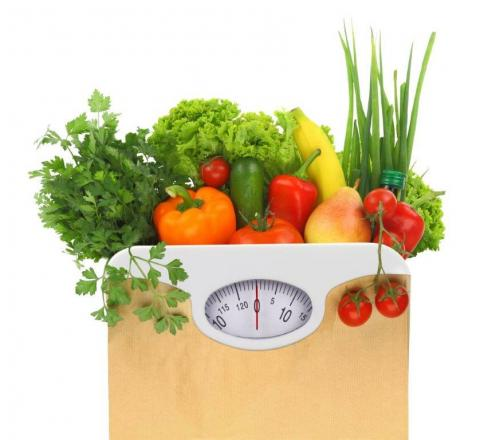 A grocery bag of vegetables sits atop an analog dial scale