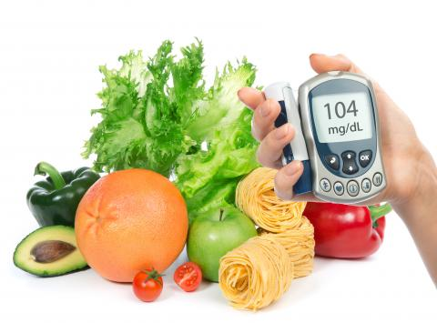 A hand holding a digital glucose monitor in front of a table full of fresh fruits and vegetables