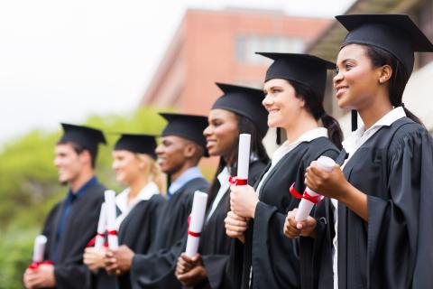 A group of high school graduates in their caps and gowns.