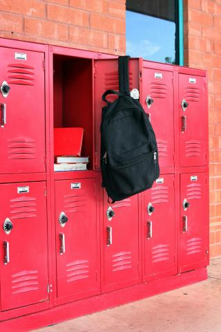 A black backpack hangs from the open door of a red school locker