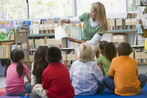 A teacher turns the pages of a picture book for a group of children
