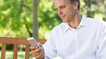A man looks at the screen of his smartphone.