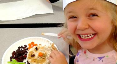 A young girl looks at her lunch plate full of healthy food.