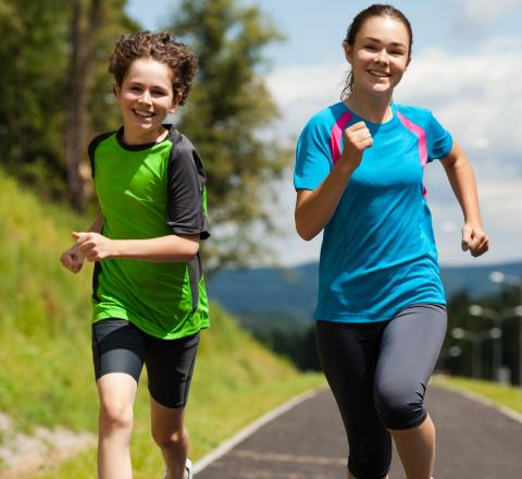 adolescent children running for exercise on an outdoor pathway