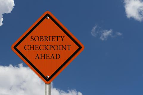 An orange diamond shaped roadsign, with the words 'Sobriety Checkpoint Ahead' in black letters.